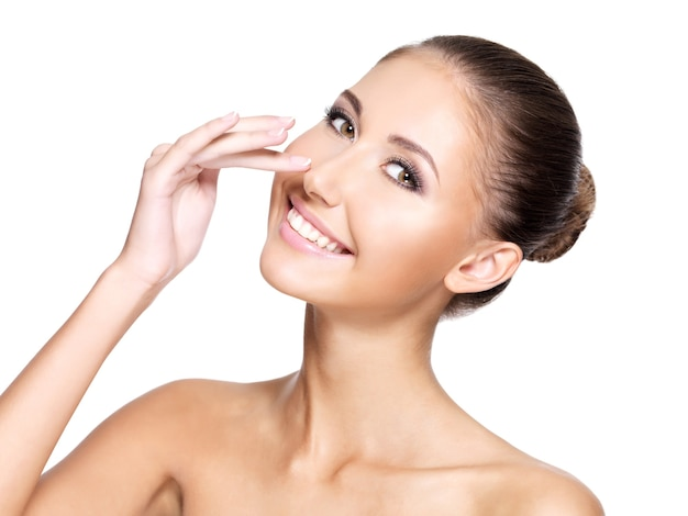 Belle jeune femme avec une peau parfaitement propre touchant son nez et souriant, isolé sur blanc