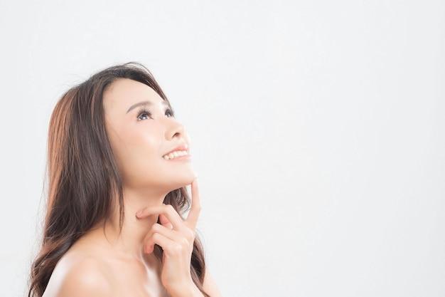 Belle jeune femme à la peau propre et fraîche, cheveux lisses, proposer un produit