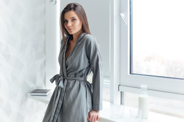 Belle jeune femme en peignoir gris debout près de la fenêtre