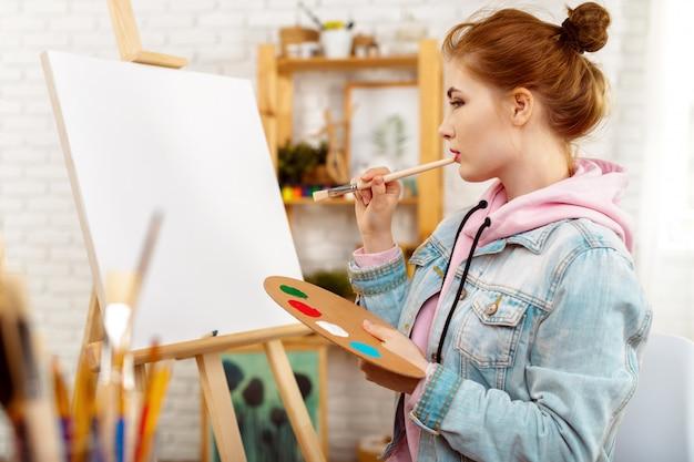 Belle jeune femme peintre au travail