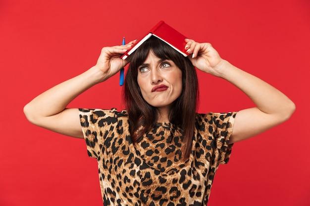 Belle jeune femme pensante vêtue d'une chemise imprimée d'animaux posant isolée sur un mur rouge avec un cahier sur la tête.