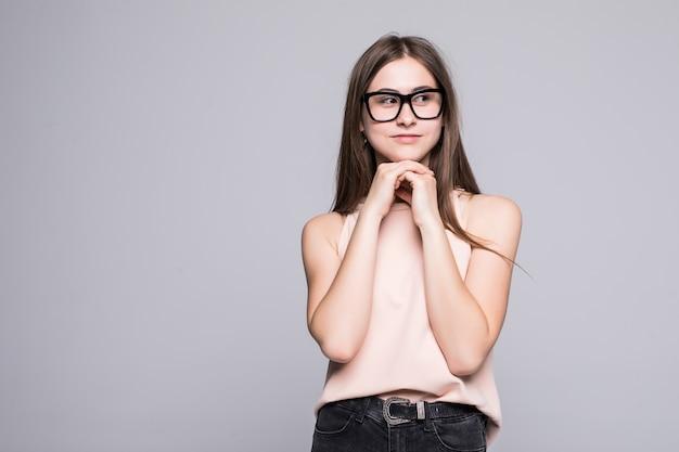 Belle jeune femme pense faire choix, isolé sur mur blanc
