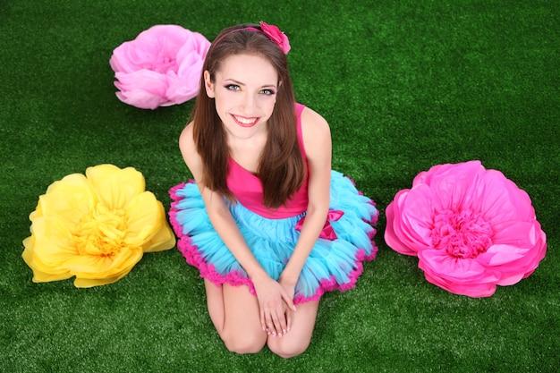 Belle jeune femme en petite jupe avec des fleurs sur l'herbe