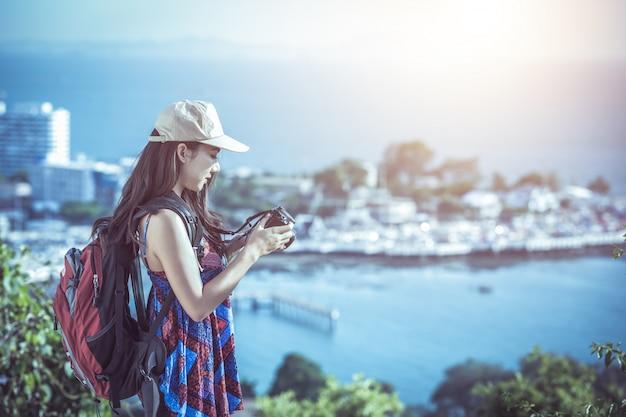 Belle jeune femme avec photographe prend une photo d'une montagne sur l'appareil photo tout en