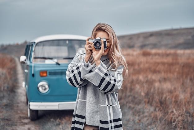 Belle jeune femme photographiant par son appareil photo rétro et souriant tout en passant du temps à l'extérieur
