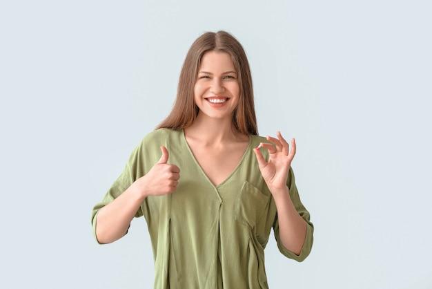 Belle jeune femme avec pilule montrant le geste du pouce vers le haut sur une surface grise