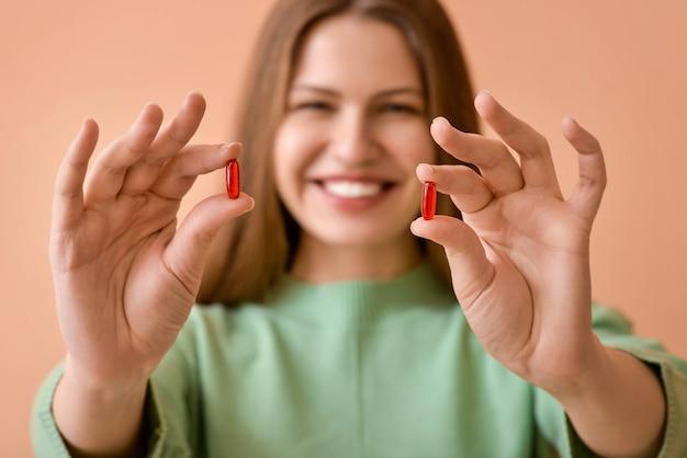 Belle jeune femme avec des pilules sur rose