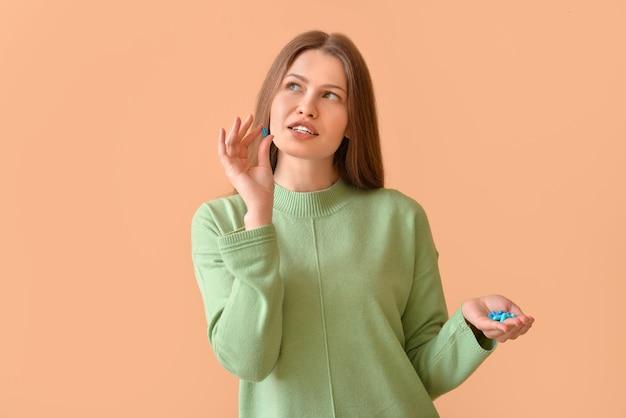 Belle jeune femme avec des pilules sur la surface de couleur