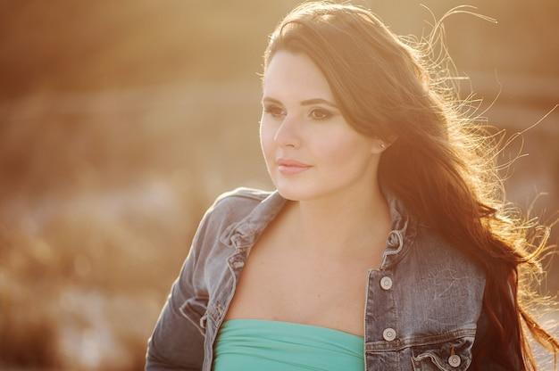 Belle jeune femme sur la plage au coucher du soleil, image extérieure et image tonique