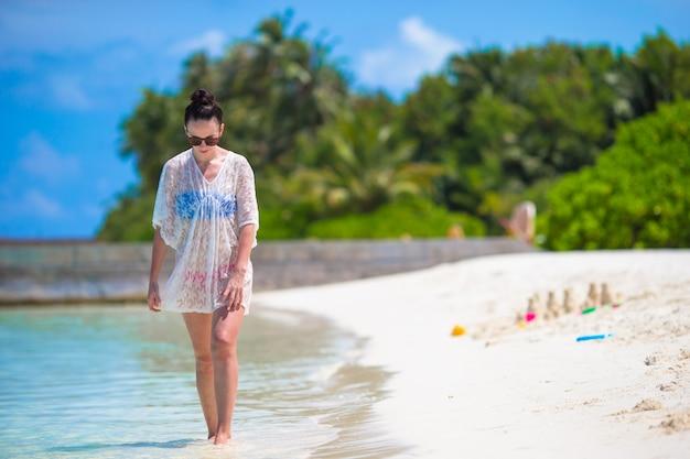 Belle jeune femme sur la plage pendant les vacances tropicales