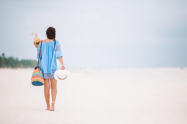 Belle jeune femme sur une plage tropicale blanche
