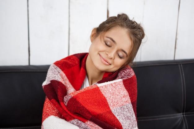 Belle jeune femme en plaid souriant, assis sur le canapé.
