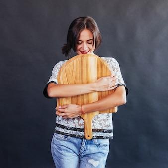 Belle jeune femme avec une planche de bois