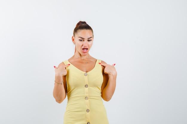 Belle jeune femme pointant sur elle-même en robe et à la vue choquée, de face.