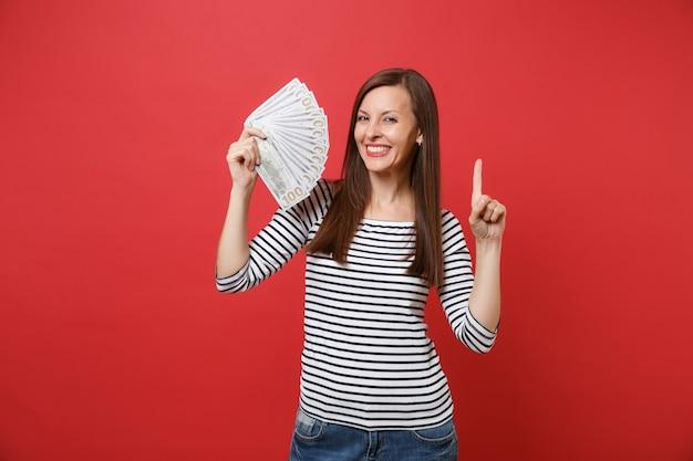 Belle jeune femme pointant l'index vers le haut et tenant beaucoup de dollars, argent comptant isolé sur fond de mur rouge vif. les gens émotions sincères, concept de style de vie. maquette de l'espace de copie.