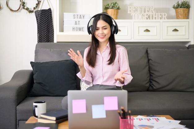 Une belle jeune femme portant un casque fait un appel de vidéoconférence via ordinateur à la maison, concept de technologie d'entreprise.
