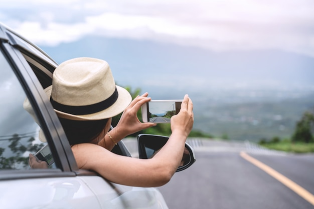 Belle jeune femme portant un chapeau blanc tissant et faisant des photos