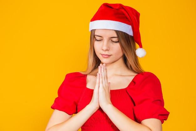 Belle jeune femme portant le chapeau de noël du père noël sur fond jaune isolé, priant les mains ensemble pour demander pardon, souriant avec confiance.