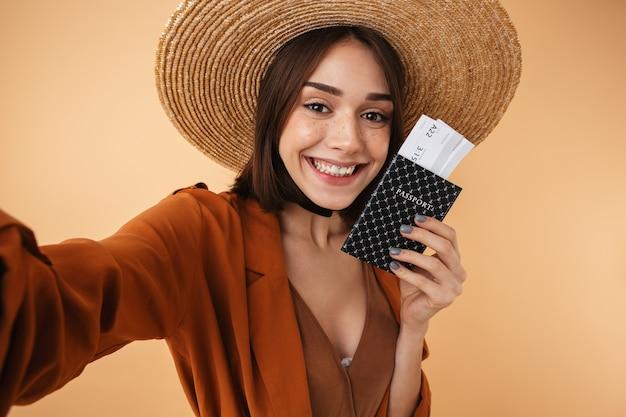Belle jeune femme portant un chapeau de paille et une tenue d'été debout isolée sur un mur beige, prenant un selfie tout en tenant un passeport avec des billets d'avion