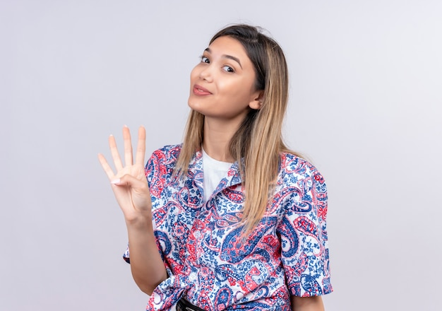 Une belle jeune femme portant une chemise imprimée paisley montrant le numéro quatre avec les doigts tout en regardant sur un mur blanc
