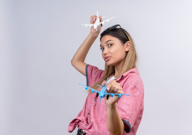 Une belle jeune femme portant une chemise rouge à lunettes de soleil à la recherche en volant des avions jouets blancs et bleus sur un mur blanc