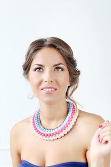 Belle jeune femme portant un collier coloré et pensant