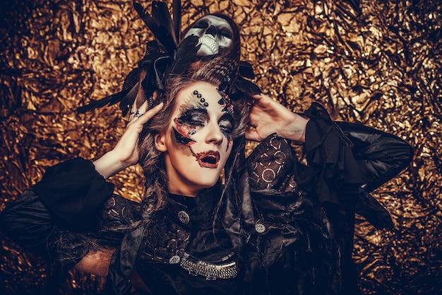 Belle jeune femme portant un costume sombre. maquillage lumineux et thème de fumée-halloween.