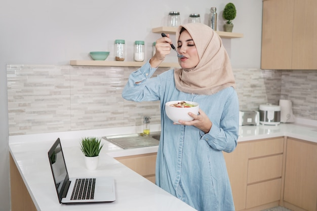 Belle jeune femme portant le hijab mangeant un bol d'esprit granola