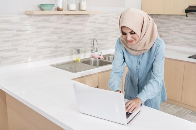 Belle jeune femme portant le hijab à la recherche de recette alimentaire sur ordinateur portable