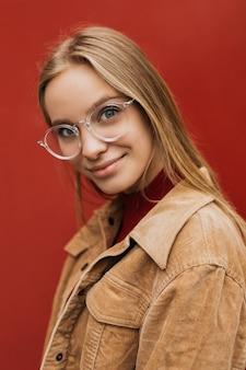 Belle jeune femme portant des lunettes élégantes, regardant la caméra, isolé sur fond rouge