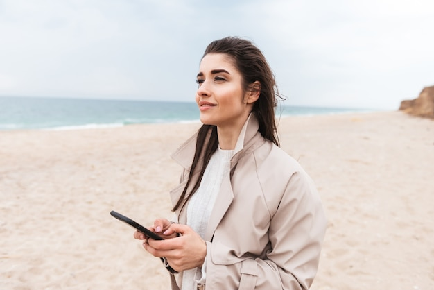 Belle jeune femme portant un manteau marchant au bord de la mer, utilisant un téléphone portable