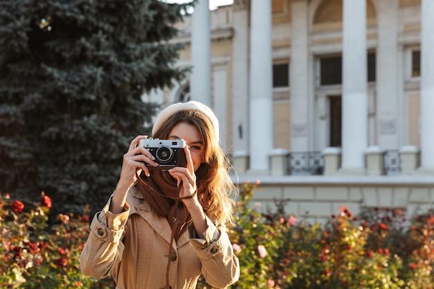 Belle jeune femme portant un manteau marchant à l'extérieur, à l'aide d'un appareil photo