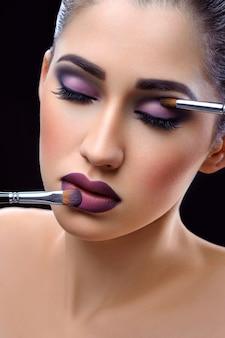 Belle jeune femme portant maquillage professionnel tenant le maquillage