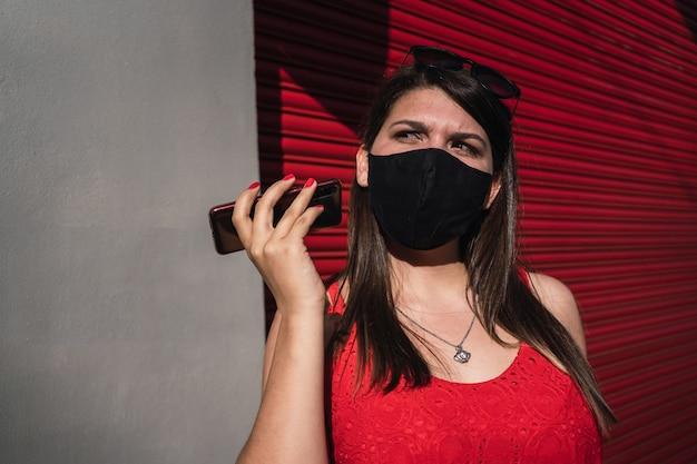 Belle jeune femme portant un masque à l'écoute d'un message audio à l'extérieur.