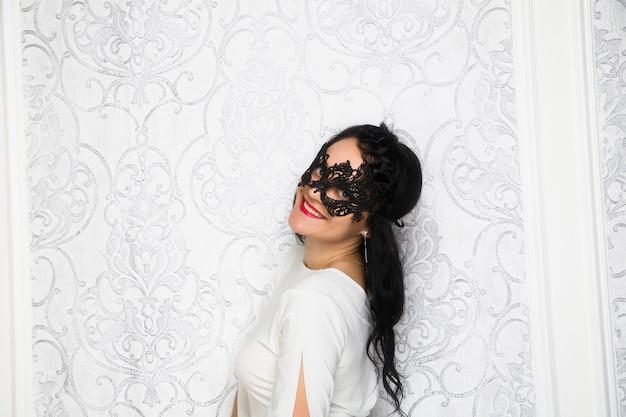 Belle jeune femme portant une robe blanche et un masque dans un style rétro