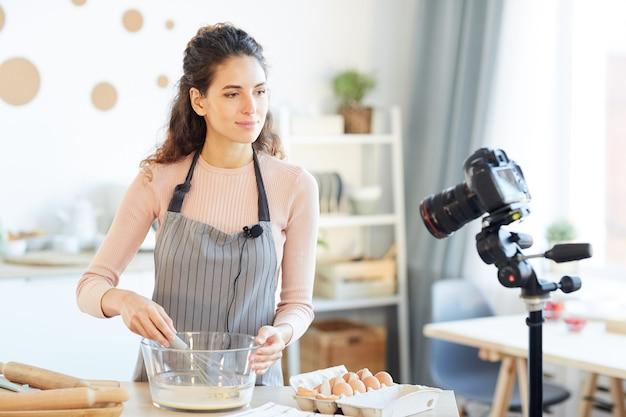 Belle jeune femme portant un tablier debout à table dans une cuisine moderne en battant des œufs à la caméra pour son blog alimentaire