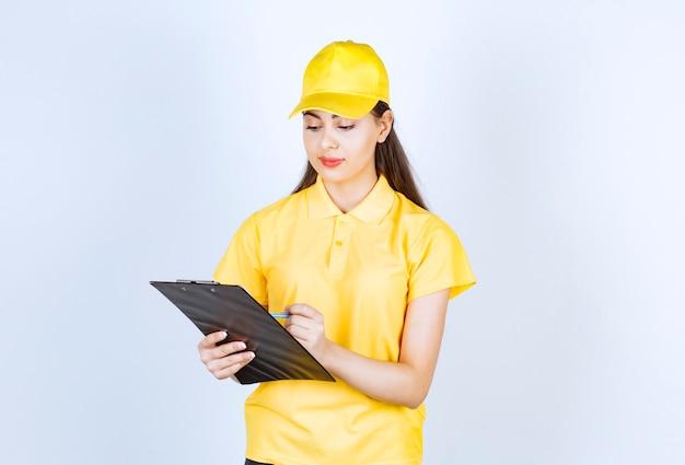 Belle jeune femme portant un uniforme de courrier jaune écrit sur le presse-papiers.