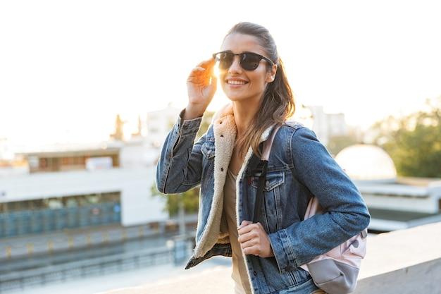Belle jeune femme portant une veste marchant à l'extérieur dans la rue de la ville