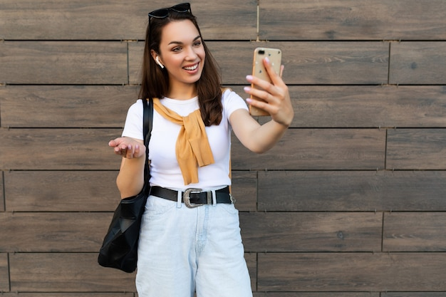 Belle jeune femme portant des vêtements décontractés debout dans la rue ayant une communication via téléphone mobile