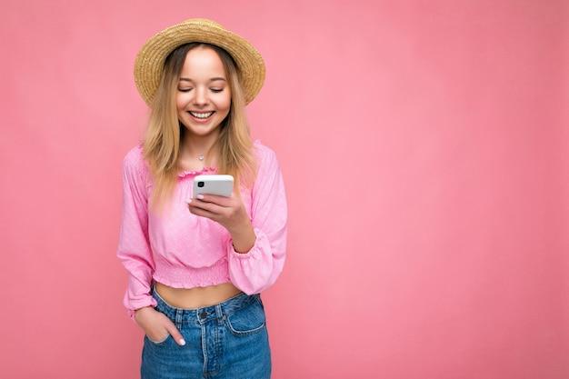Belle jeune femme portant des vêtements décontractés debout isolé sur fond surfant sur internet par téléphone en regardant l'écran mobile