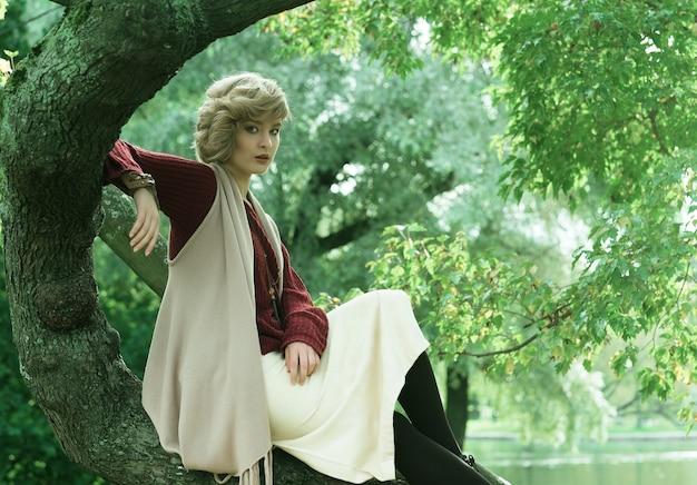 Belle jeune femme posant sur un arbre