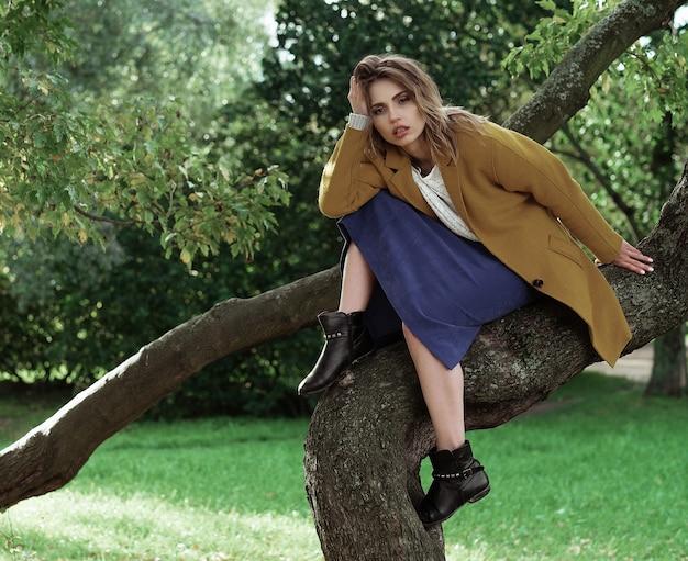 Belle jeune femme posant sur un arbre.