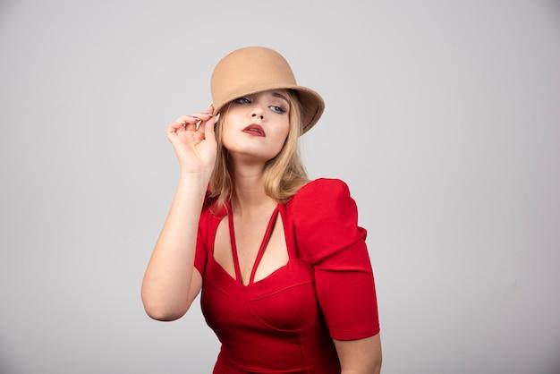 Belle jeune femme posant avec chapeau.