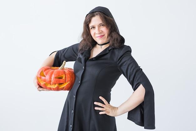 Belle jeune femme posant avec citrouille jack-o'-lantern