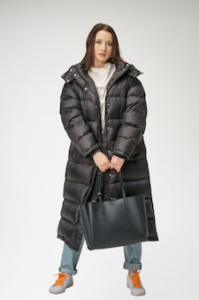 Belle jeune femme posant dans un long manteau d'hiver sur un fond blanc