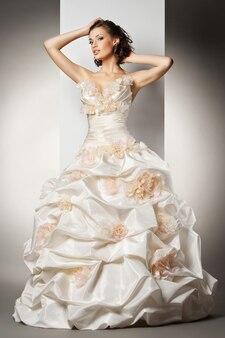 La belle jeune femme posant dans une robe de mariée sur fond gris