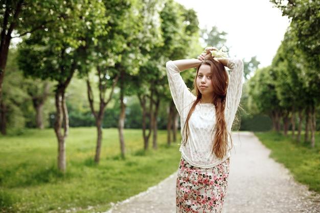 Belle jeune femme posant dans la ruelle du parc