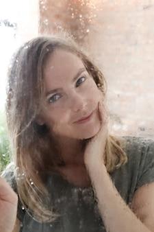 Belle jeune femme posant derrière une fenêtre humide