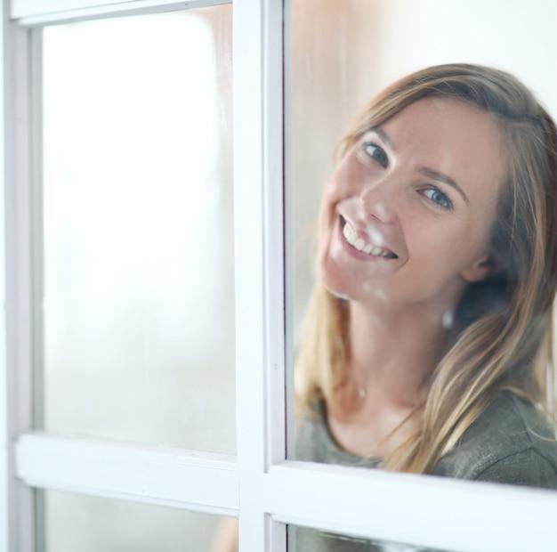 Belle jeune femme posant derrière la fenêtre