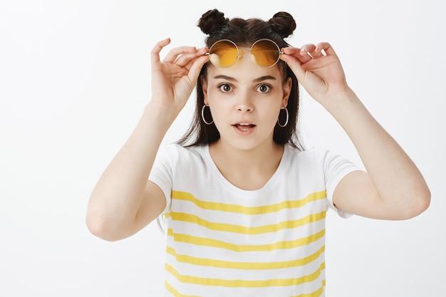 Belle jeune femme posant avec des lunettes de soleil contre le mur blanc